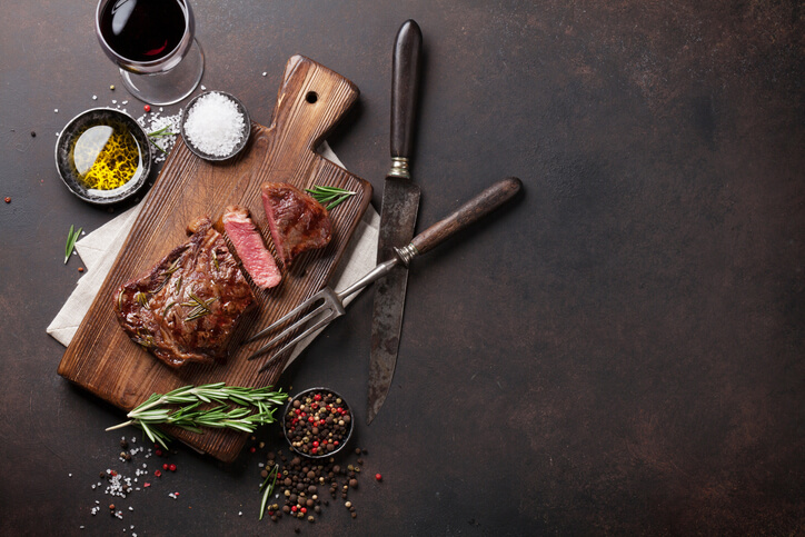 A steak board accompanied by seasoning and a glass of red wine